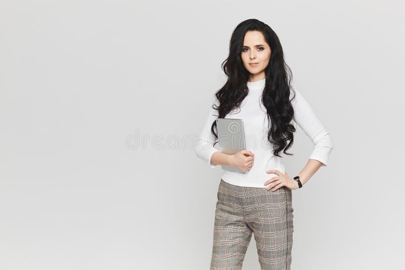 Mulher de negócios nova e bonita na blusa branca e nas calças de manta elegantes com a tabuleta em suas mãos fotos de stock royalty free