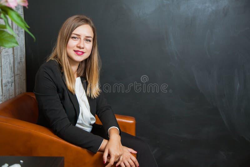 Mulher de negócios nova e bonita no olhar da poltrona na câmera fotos de stock