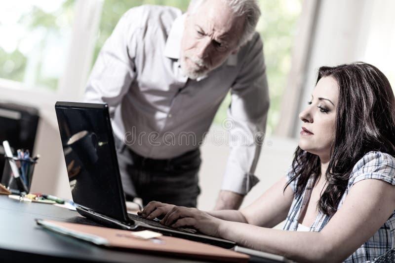 Mulher de negócios nova e homem de negócios superior que trabalham junto imagens de stock
