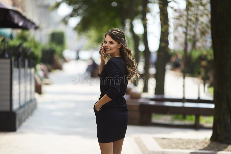 A mulher de negócios nova e sorrindo em um vestido preto à moda vai a uma reunião pela rua da cidade do verão imagens de stock