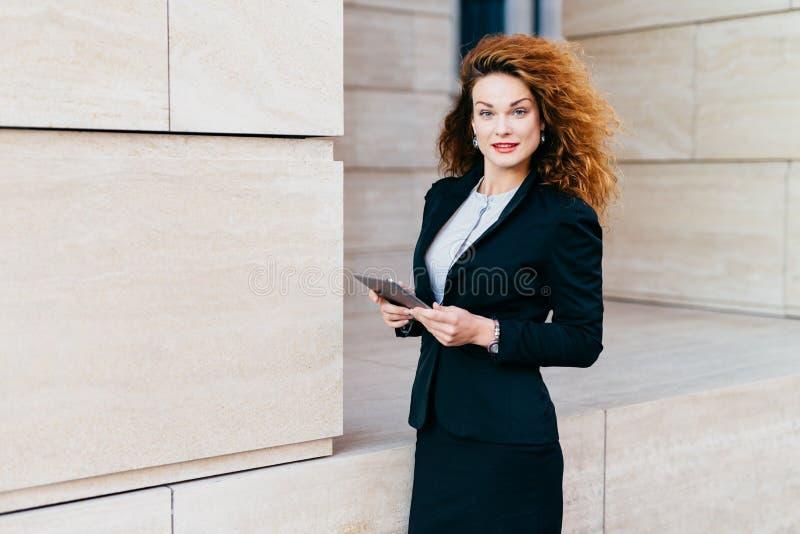 Mulher de negócios nova elegante bonita no traje preto, tendo o cabelo encaracolado espesso e aparência atraente, guardando a tab fotos de stock