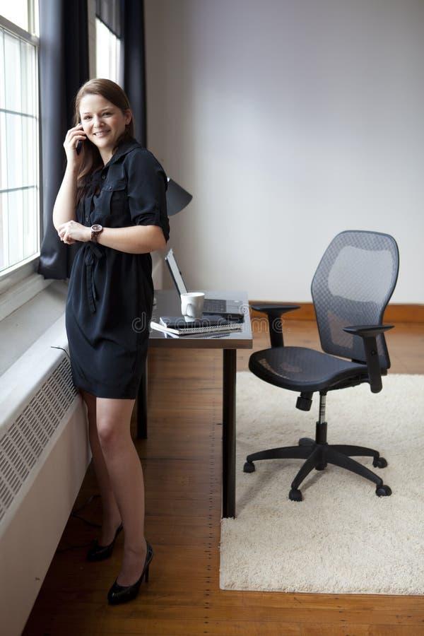 Mulher de negócios nova em um telefone celular fotografia de stock royalty free
