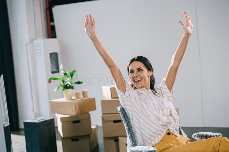 mulher de negócios nova entusiasmado que levanta as mãos e que olha afastado fotografia de stock