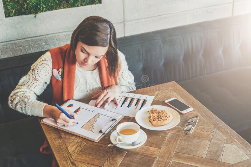A mulher de negócios nova está sentando-se no café na tabela, trabalhando A mulher está olhando cartas, gráficos, diagramas fotos de stock royalty free