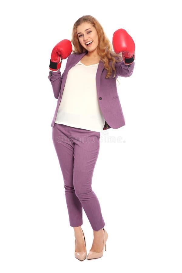 Mulher de negócios nova feliz com luvas de encaixotamento que comemora a vitória no branco fotografia de stock