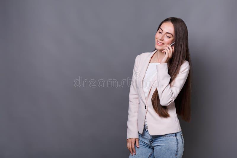 Mulher de negócios nova feliz que fala no telefone foto de stock royalty free