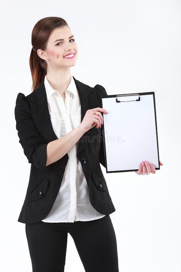 Mulher de negócios nova feliz que guarda o papel vazio na prancheta no wh imagens de stock