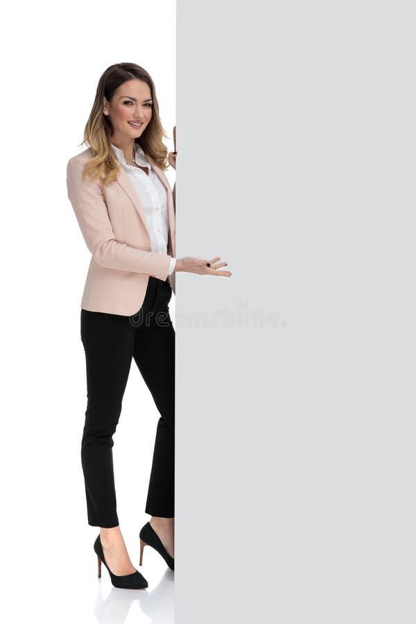 A mulher de negócios nova guarda a mensagem vazia do sinal e dos presentes foto de stock