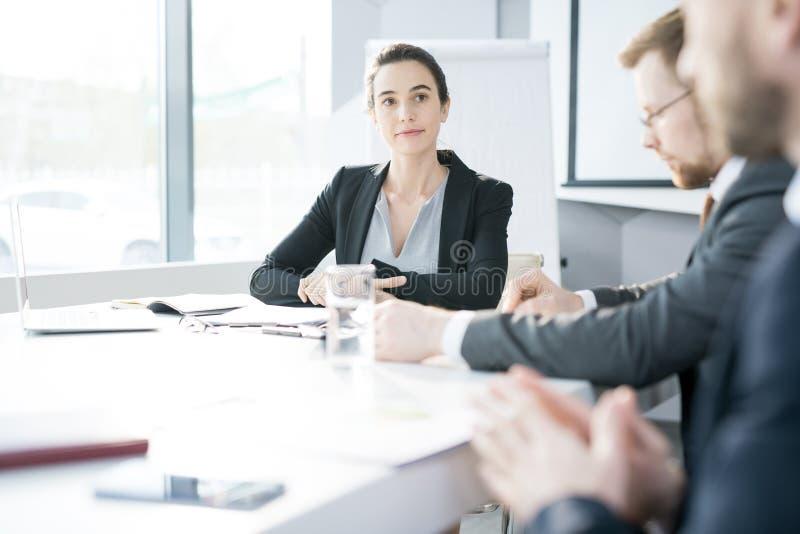 Mulher de negócios nova Listening na reunião imagem de stock