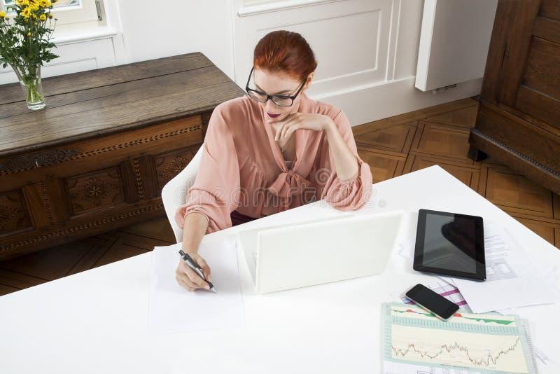 Mulher de negócios nova Looking no computador seriamente imagens de stock royalty free