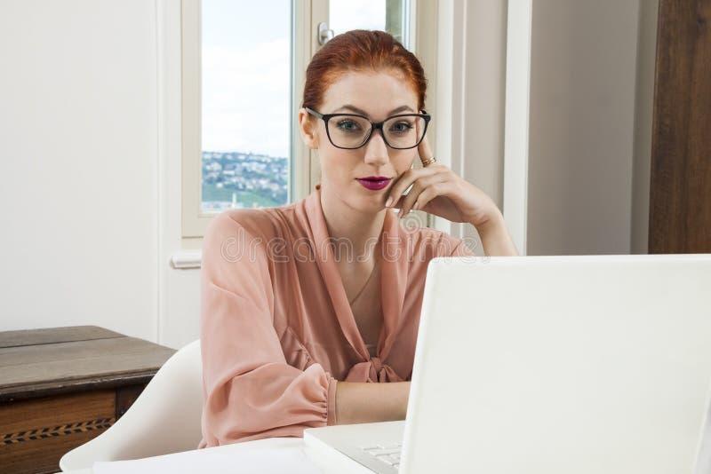 Mulher de negócios nova Looking no computador seriamente fotografia de stock royalty free