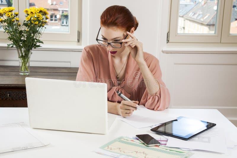 Mulher de negócios nova Looking no computador seriamente fotografia de stock
