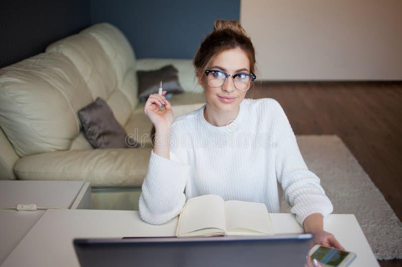 Mulher de negócios nova Menina bonita com funcionamento de vidros em casa com portátil imagem de stock