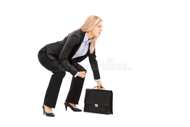 Mulher de negócios nova na posição da luta romana de suco que guarda a mala de viagem imagem de stock royalty free