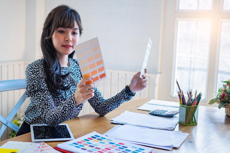 Mulher de negócios nova na roupa ocasional no espaço de escritório domiciliário do negócio da partida, mulher criativa asiática n fotos de stock