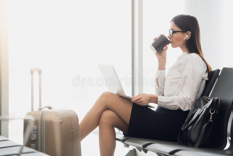 Mulher de negócios nova no aeroporto, usando o portátil e bebendo o café, o curso, a viagem de negócios e conceito ativo do estil imagens de stock