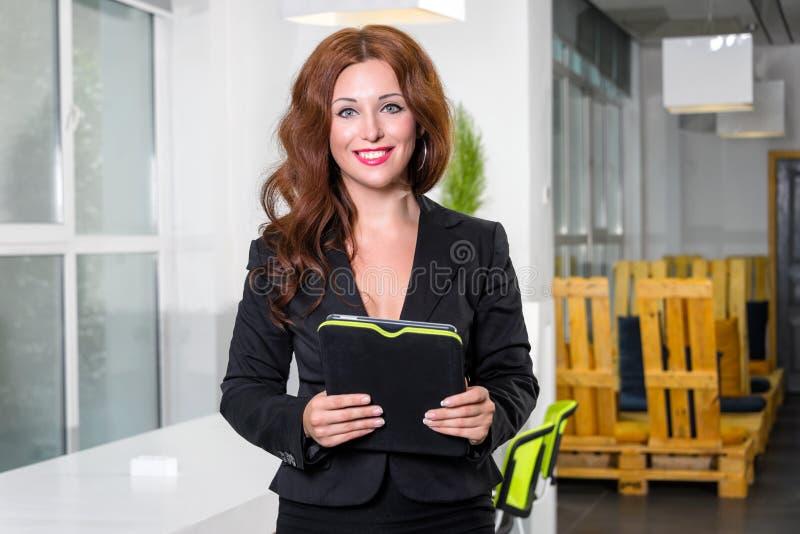 Mulher de negócios nova no escritório brilhante moderno que guarda a tabuleta com uma lista de tarefas que olham a câmera e o sor imagens de stock