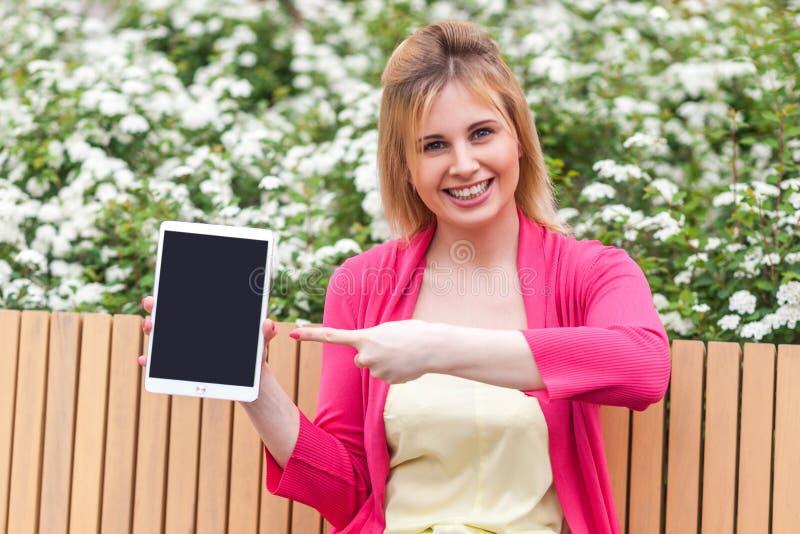 Mulher de negócios nova no estilo da elegância que senta-se no banco no parque, guardando a tela vazia da tabuleta e apontando o  foto de stock