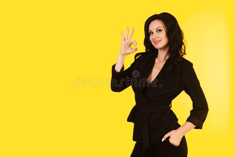 A mulher de negócios nova no terno preto mostra a aprovação do sinal isolado em um fundo amarelo fotografia de stock royalty free