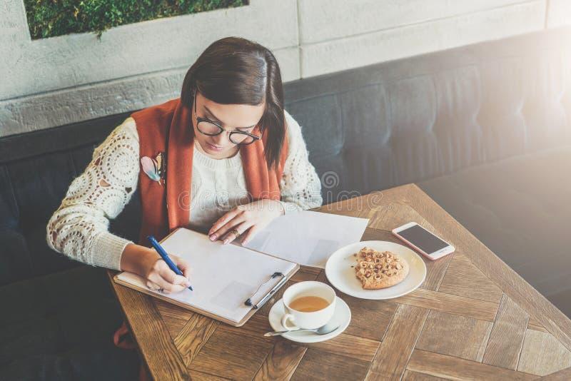 A mulher de negócios nova nos vidros e na camiseta branca está sentando-se no café na tabela, originais de assinatura, trabalhand fotografia de stock
