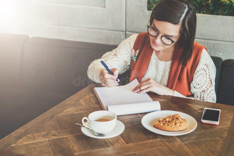A mulher de negócios nova nos vidros e na camiseta branca está sentando-se no café na tabela, trabalhando A menina analisa dados imagem de stock royalty free