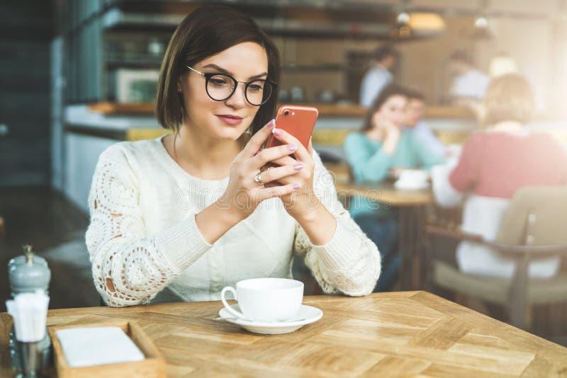 A mulher de negócios nova nos vidros e na camiseta branca está sentando-se no café na tabela e está usando-se o smartphone, traba imagem de stock