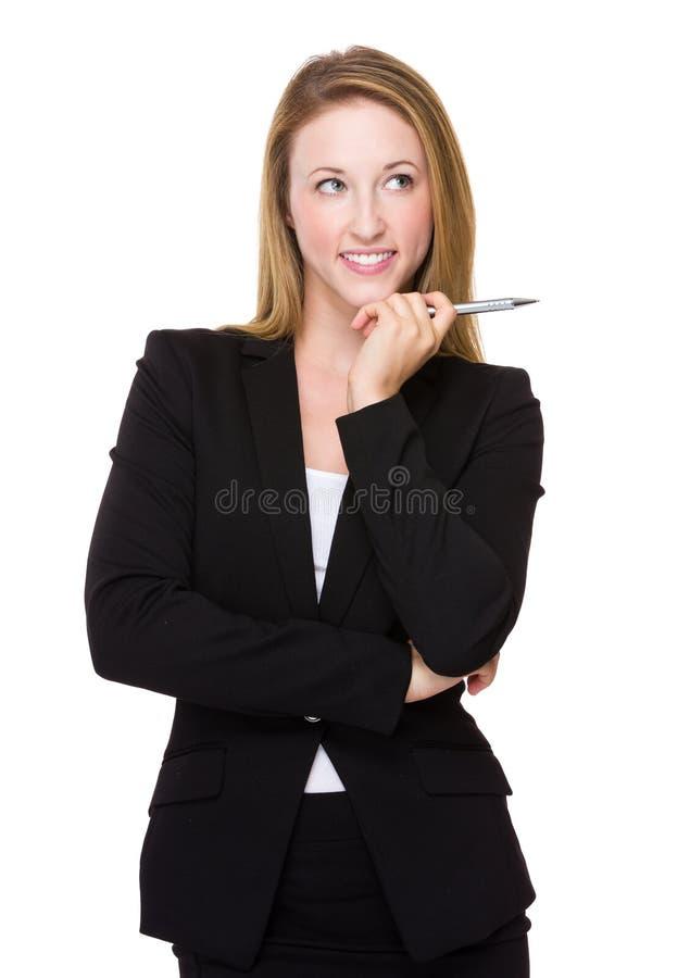 A mulher de negócios nova pensa de uma ideia com guardar uma pena imagem de stock