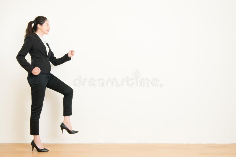 Mulher de negócios nova que anda acima em etapas da carreira imagens de stock