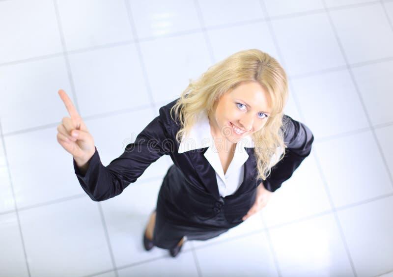 Mulher de negócios nova que aponta seu dedo acima fotografia de stock