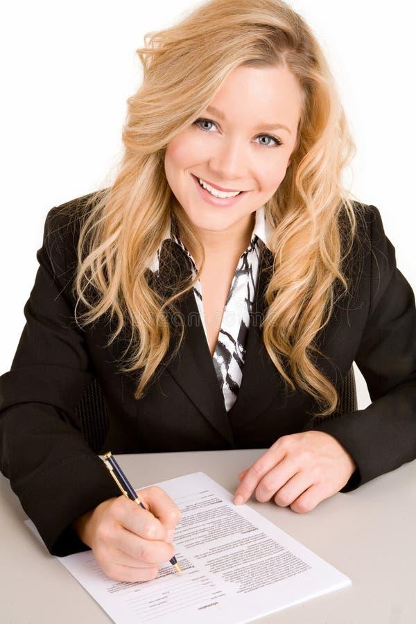 Mulher de negócios nova que assina um original fotografia de stock royalty free