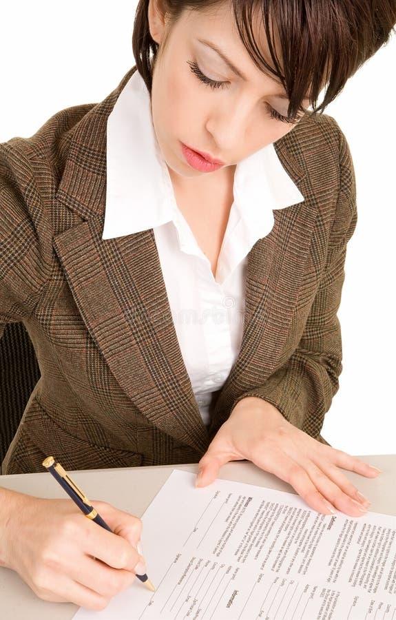 Mulher de negócios nova que assina um original fotos de stock royalty free
