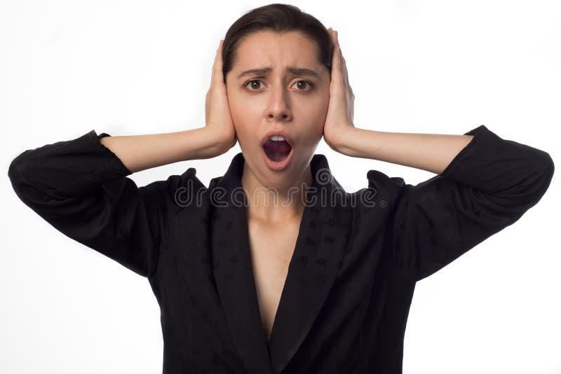 Mulher de negócios nova que cobre sua boca aberta orelhas foto de stock royalty free