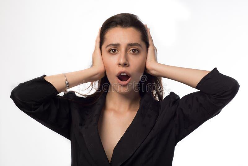 Mulher de negócios nova que cobre suas orelhas e gritaria sobre o fundo branco fotografia de stock