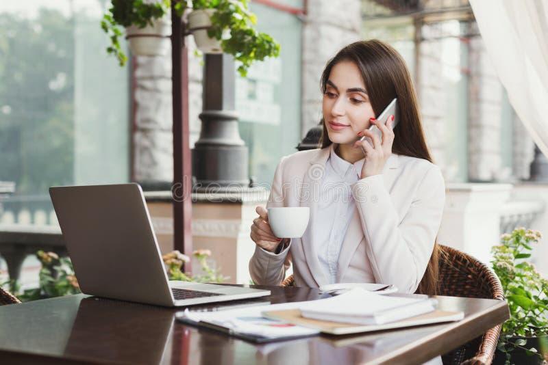 Mulher de negócios nova que fala no telefone e no café bebendo fora imagens de stock royalty free