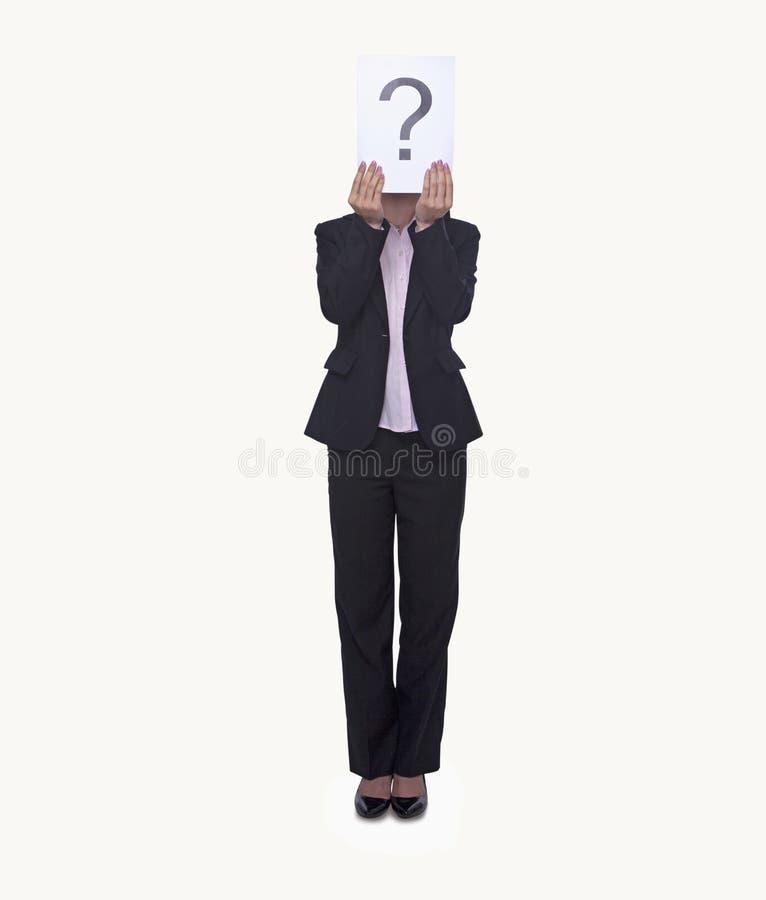Mulher de negócios nova que guarda no papel com um ponto de interrogação nele, cara obscurecida, tiro do estúdio fotos de stock