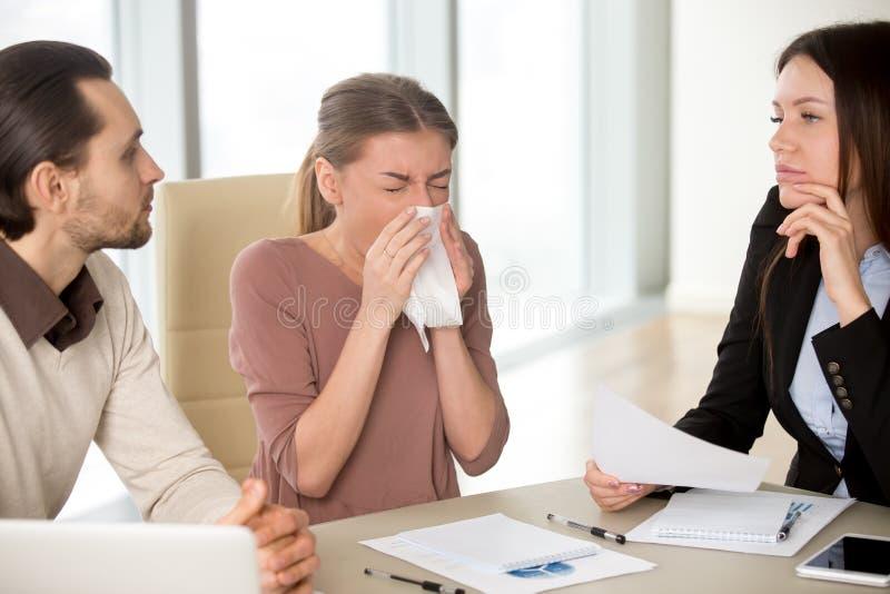 Mulher de negócios nova que guarda o lenço que espirra durante a reunião foto de stock royalty free
