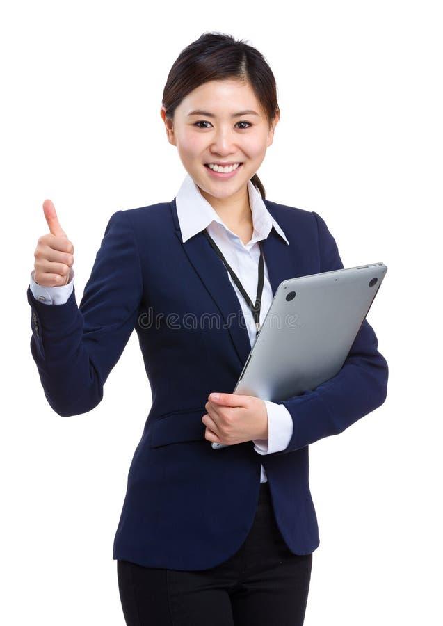 Mulher de negócios nova que guarda o portátil com polegar acima fotografia de stock
