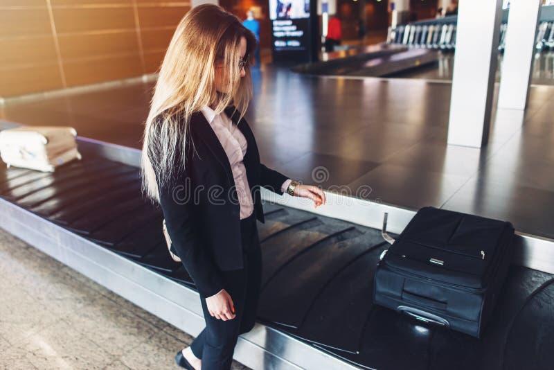 Mulher de negócios nova que obtém lhe a bagagem da reivindicação de bagagem no aeroporto imagens de stock royalty free