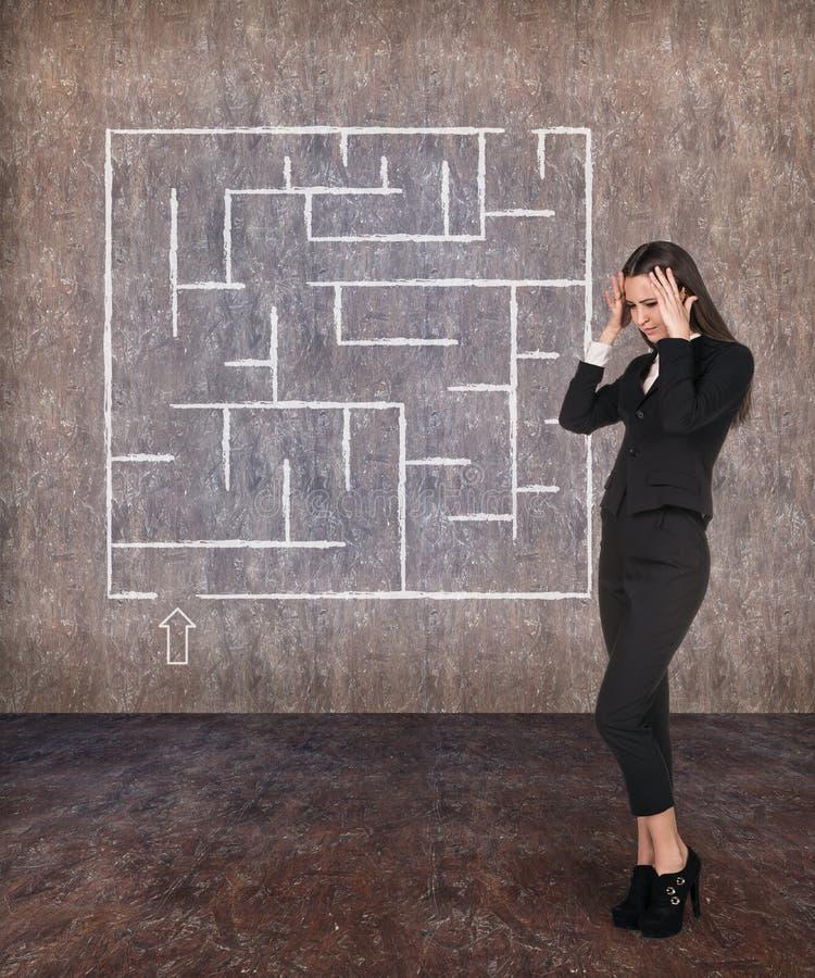 Mulher de negócios nova que olha o labirinto foto de stock