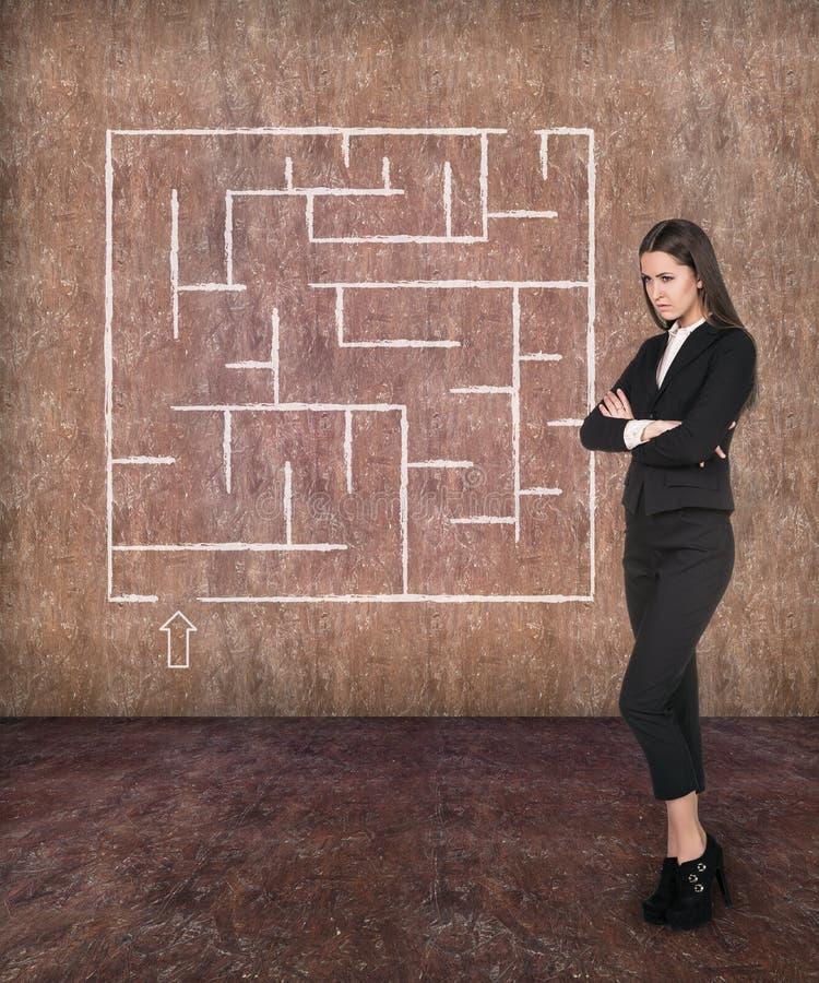 Mulher de negócios nova que olha o labirinto imagens de stock royalty free