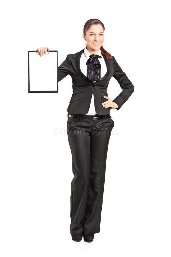 Mulher de negócios nova que prende uma prancheta vazia imagem de stock royalty free