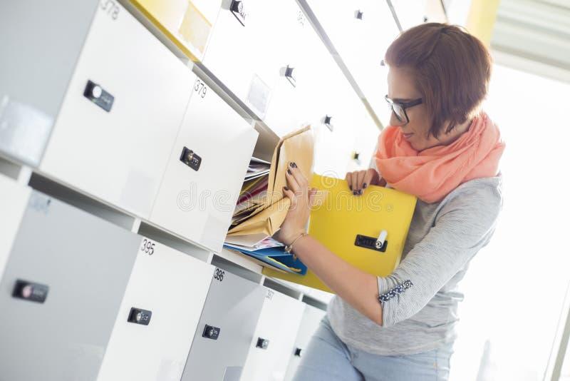 Mulher de negócios nova que remove o arquivo do cacifo no escritório criativo imagem de stock