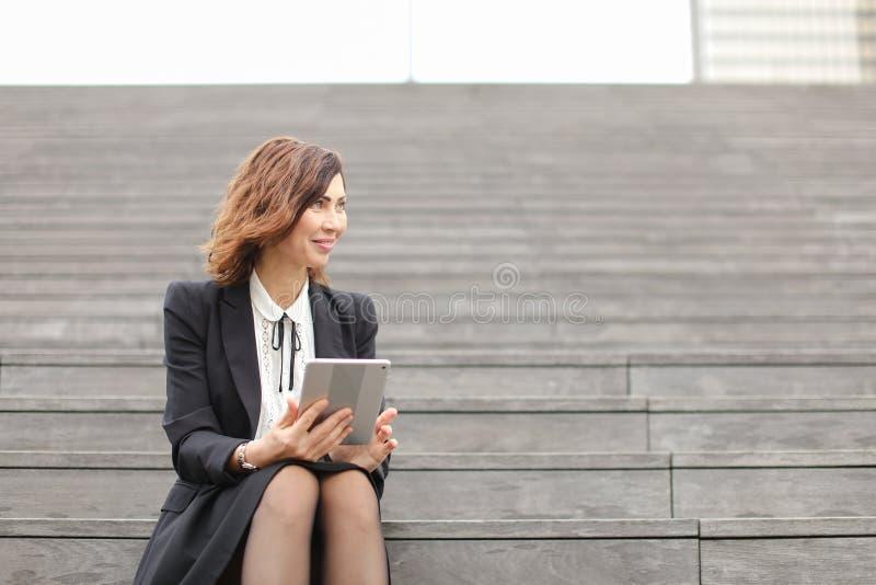 Mulher de negócios nova que senta-se em escadas com tabuleta e trabalho foto de stock royalty free