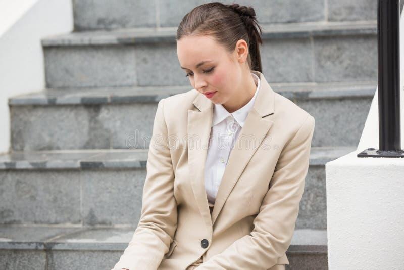 Mulher de negócios nova que senta-se em etapas fotografia de stock