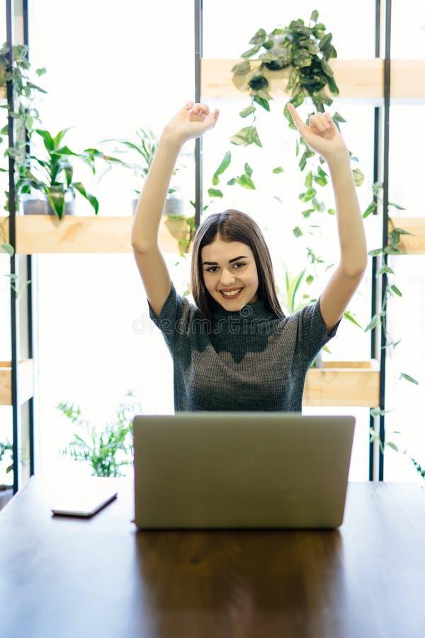 Mulher de negócios nova que senta-se em uma mesa de escritório na frente do portátil com suas mãos acima imagem de stock