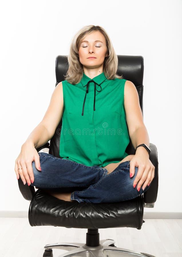 Mulher de negócios nova que senta-se na cadeira que faz o exercício da aptidão no local de trabalho fotografia de stock