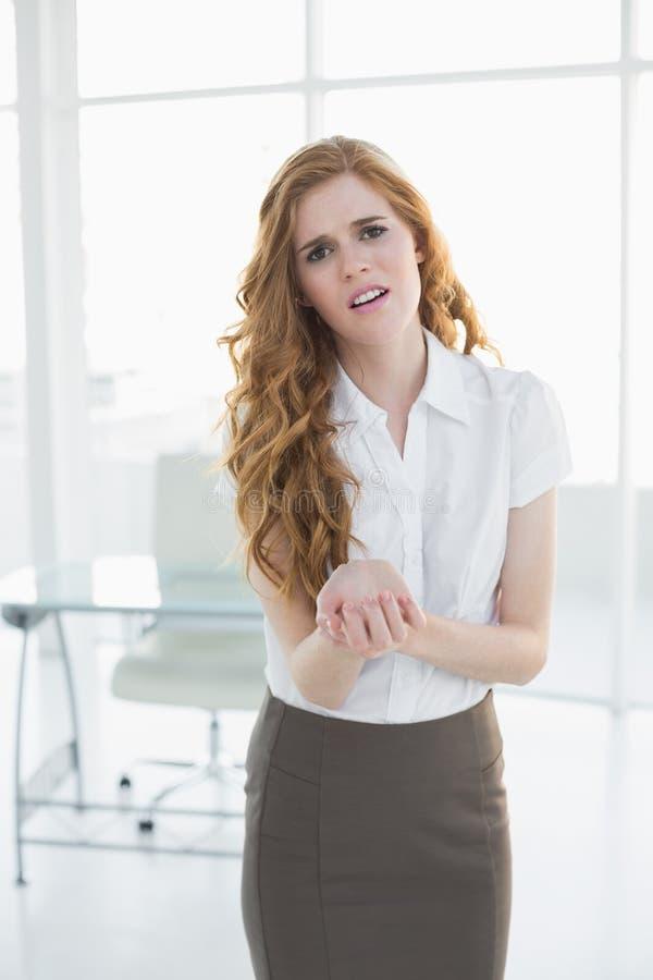 Mulher de negócios nova que sofre da dor do pulso no escritório fotos de stock royalty free