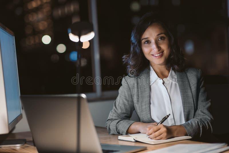 Mulher de negócios nova que sorri ao trabalhar horas extras em seu escritório foto de stock royalty free