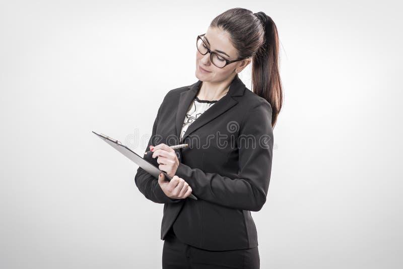 Mulher de negócios nova que toma notas imagem de stock