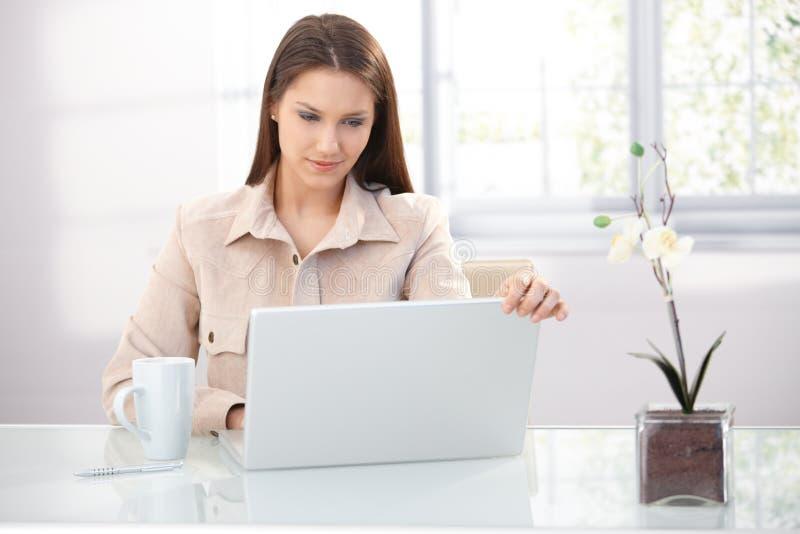 Mulher de negócios nova que trabalha em casa foto de stock